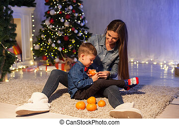 mom with sons eat tangerines new year Christmas tree gifts