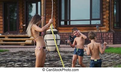 Mom with two kids playing with garden hose pouring water on the grass