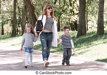 mom with two kids walking in the city Park