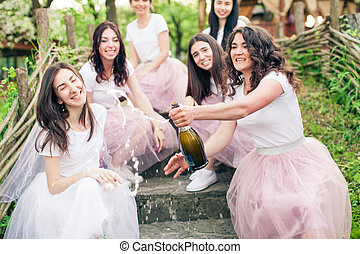 Moment of champagne bottle opening while hen party