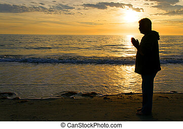 The silhouette of a man standing on the beach praying with a golden sunset behind him.