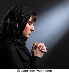 Moment of quiet faith as young woman prays - Faith of young...