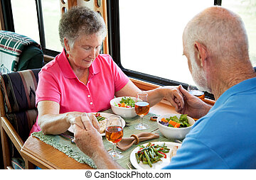 Senior couple says a prayer over a healthy turkey dinner served in the kitchen of their mobile home.