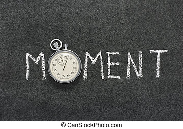 moment word handwritten on chalkboard with vintage precise stopwatch used instead of O