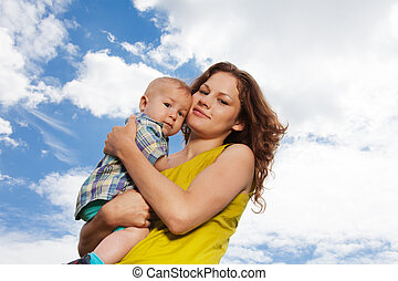 mommy holding her baby in park