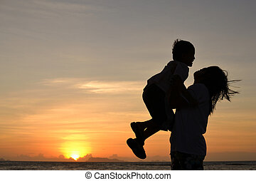 mommy love - silhouette of mommy and small boy on the beach...