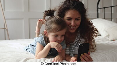 Mommy lying on bed with cute daughter, making selfie photos.