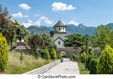 Monastery on the river Moraca amid mountains in the background.