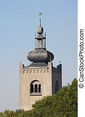 Monastery tower behind tree tops