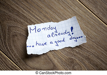 Monday already written on piece of paper, on a wood background.