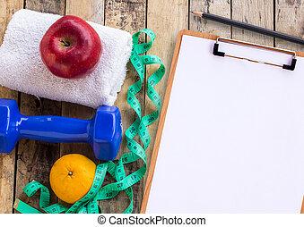 monde médical, formulaire, à, bleu, haltère, serviette blanche, mètre ruban, et, pomme rouge, sur, bois, table.