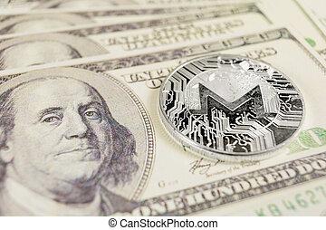 MONERO coin on the background of Dollar bills
