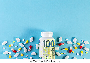 Money and pills of different colors on blue background. Rising cost of health care.