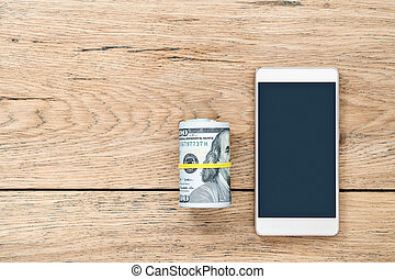 Money and smartphone on a wooden table