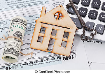 Money and wooden house with calculator on tax form background