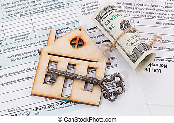 Money and wooden house with vintage key on tax form background
