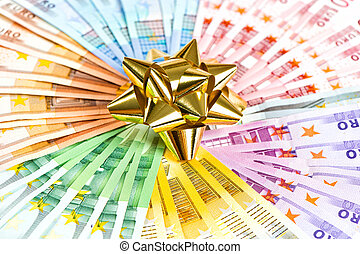 money as a gift. golden ribbon on euro banknotes background
