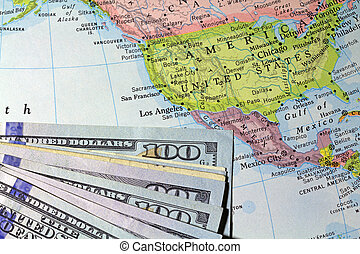 Money atop an old atlas - A partial view of hundred dollar ...