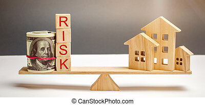 Money bag, blocks with the word Risk and a wooden house on the scales. The concept of losing money when investing in real estate. Risks of losing a home or housing for non-payment. Property insurance