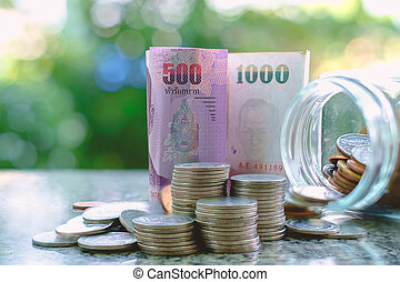 Money banknote and coins in the glass jar, Thai currency on blurred natural green background