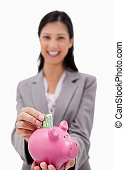 Money being put into piggy bank by smiling businesswoman