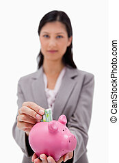 Money being put into piggy bank by businesswoman
