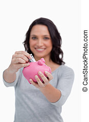 Money being put into piggy bank by woman