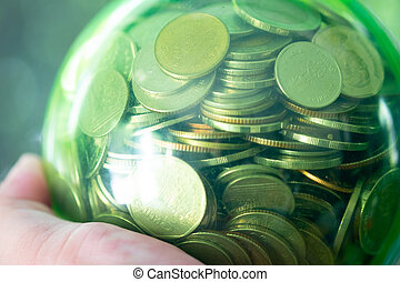 Money coins Thai baht in a green round jar on hand