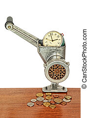 Alarm clock in manual meat grinder and coins on wooden table.
