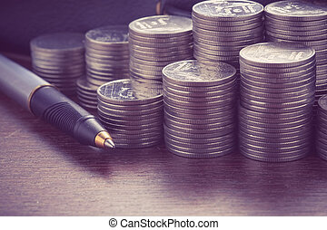 money concept coins and pen with filter effect retro vintage...