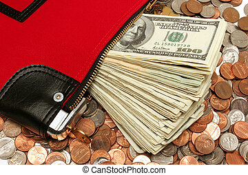 close up of a red money bag on coins with an extruding pile of bank notes