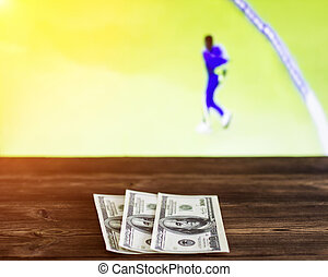 Money dollars on the background of a TV on which there is a sport game of cricket, sports betting, cricket