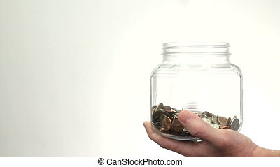 Money Dropping Into Jar Bank - Money coins drop into a glass...