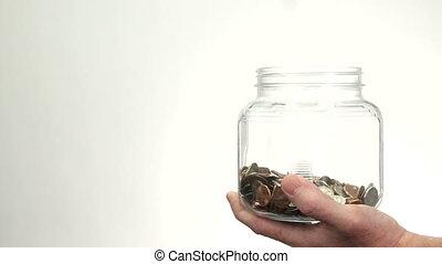 Money Dropping Into Jar Bank