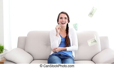 Money falling on pretty brunette on the couch at home in the...