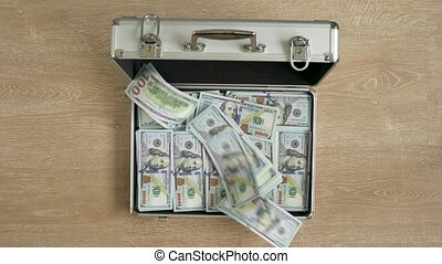 Money falls in a suitcase and it closes