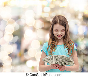 smiling little girl looking at dollar cash money - money, ...