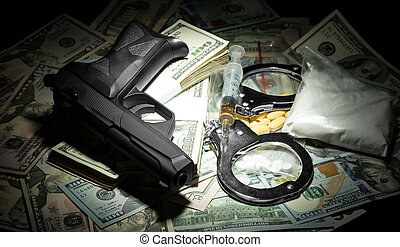 Money, gun and drugs in the dark, closeup