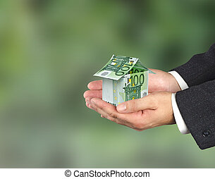 Money home and hand isolated on white background