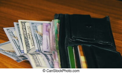 Money in a Wallet Rotating on a Wooden Table