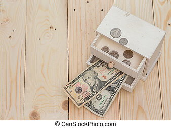 Money in the box on wooden background
