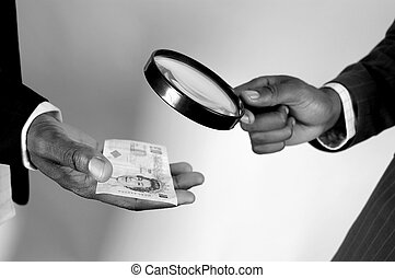 This is an image of the hands of two men checking the legitimacy of a ten pound note (uk money).