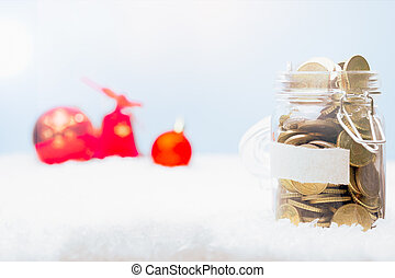 Money jar and ornaments in Christmas snow landscape