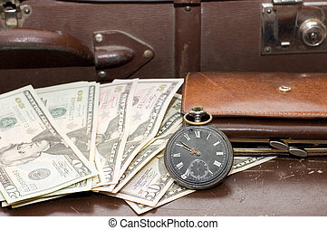 Money lays on an old suitcase