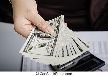 Money maker - Businesswoman holding money over calculator