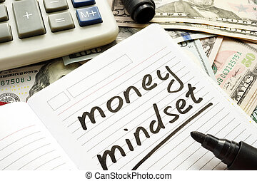 Money mindset handwritten in a note and dollar banknotes.