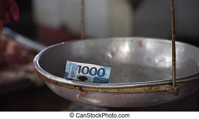 Money on the scales in the street market .
