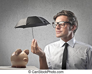 money safe - businessman with umbrella protects bank