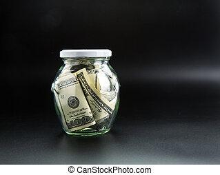 Money saving concept, glass jar full of dollars