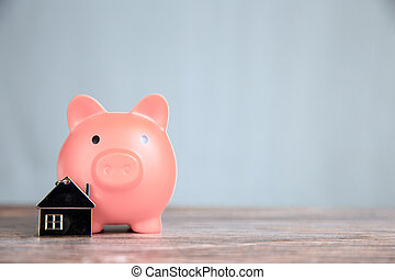 Money saving for buying a new house in pink piggy bank , real estate,mortgage,loans,business concept with space for text copy space